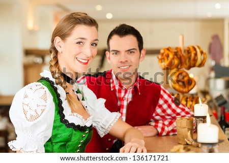 Young couple in traditional Bavarian Tracht in restaurant or pub with pretzel - stock photo