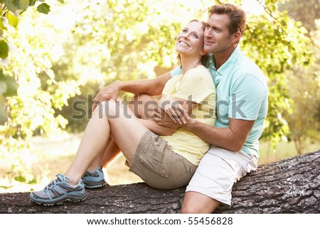 Young Couple In Walking Clothes Resting On Tree In Park