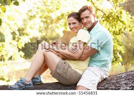 Young Couple In Walking Clothes Resting On Tree In Park - stock photo