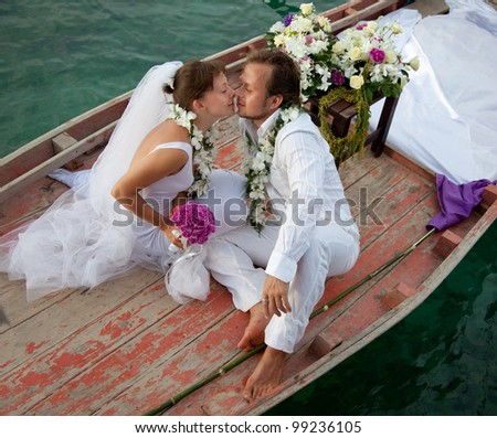 young couple in wedding dress kissing in the boat - stock photo