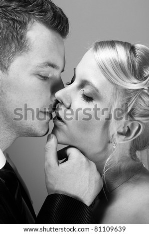 young couple in wedding wear kissing