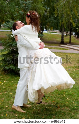 young couple in wedding wear walking in the park