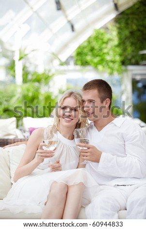 Young couple in white with glasses in their hands at a restaurant - stock photo