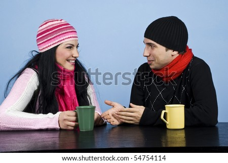 Young couple in winter clothes standing at table  enjoying a cup of hot drink and having a funny conversation and they laughing together - stock photo