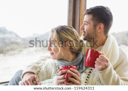 Young couple in winter clothing with coffee cups looking out through cabin window - stock photo