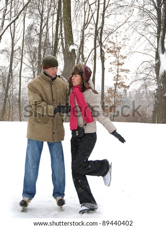 young couple in winter skate rink - stock photo