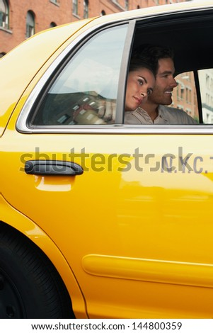 Young couple in yellow taxi on urban street - stock photo