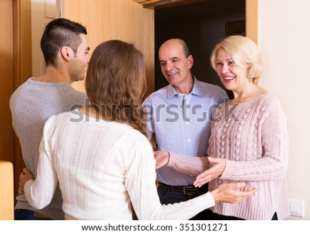 young couple inviting elderly parents to come inside - stock photo