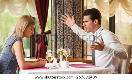 Young couple is arguing in restaurant - stock photo