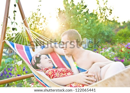 young couple is cuddling in a hammock. They are smiling . Horizontally framed shot. - stock photo