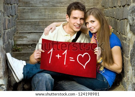 Young couple is holding board with romantic symbol. - stock photo