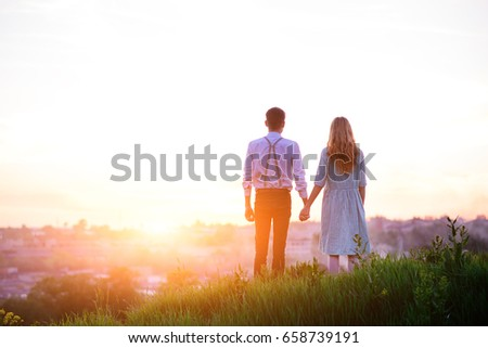 young couple is holding hands on a background sunset.