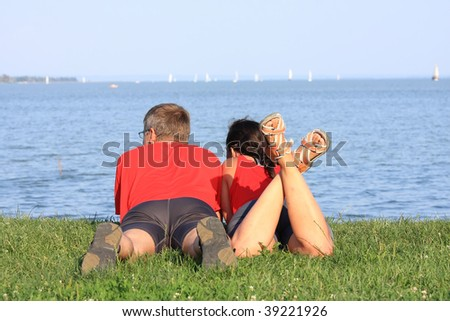 Young couple is laying by the shore of the lake - stock photo