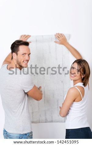 Young couple is looking for a new wallpaper - stock photo