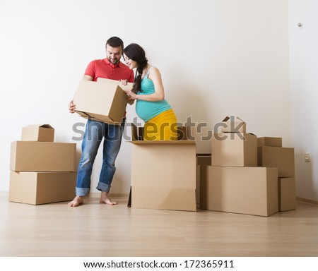 Young couple is moving into new house with lot of boxes. Woman is pregnant. - stock photo