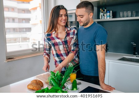 Young couple is preparing dinner. Girl is cutting food. Man is hugging her