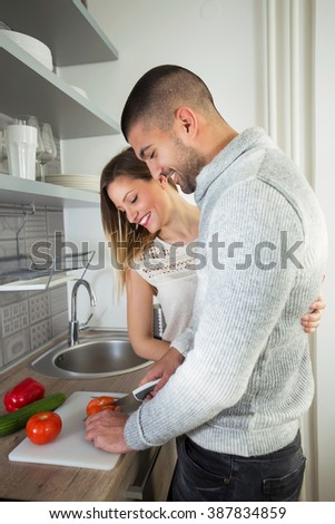 Young couple is preparing dinner in the kitchen. They are preparing vegetables. - stock photo