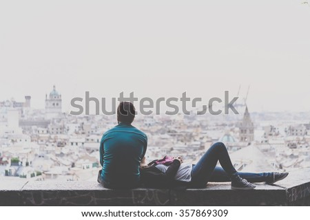 Young couple is relaxing and enjoying the view of the city. Toned picture - stock photo