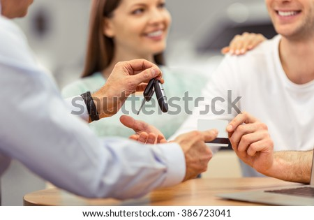 Young couple is smiling while buying a car, middle aged worker of a motor show is giving keys, close-up - stock photo