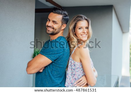 Young couple is standing back to back at the balcony and smiling. City background.