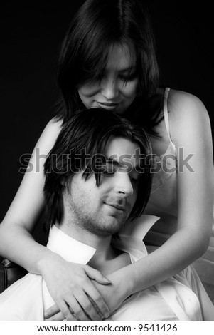 young couple isolated on black, black and white