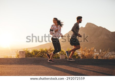 Young couple jogging early in morning, with woman looking back over her shoulder. Young man and woman running outdoors on a country road. - stock photo