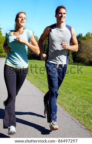 Young couple jogging in park. Health and fitness. - stock photo