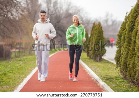 Young couple jogging on the running track in the park - stock photo