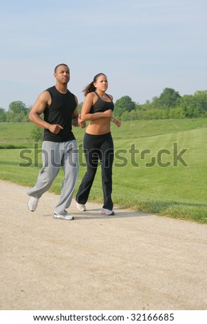 Young Couple Jogging Outdoor at Park under Summer Sky - stock photo