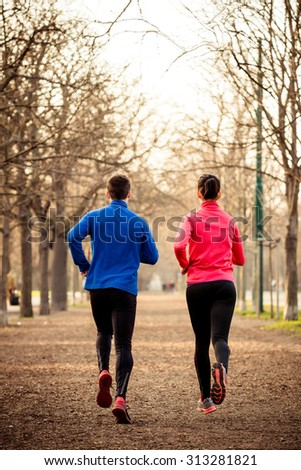 Young couple jogging together in late autumn nature - rear view - stock photo