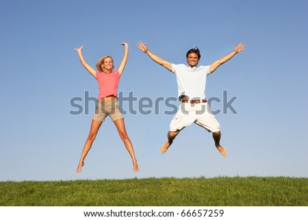 Young couple jumping in air - stock photo