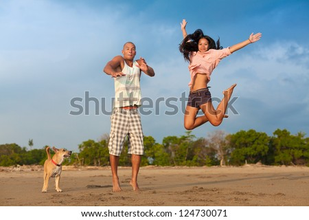 young couple jumping in the air on the beach with their dog
