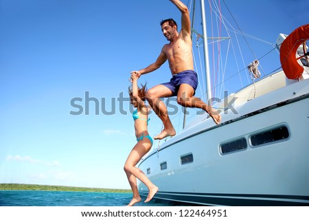 Young couple jumping in water from yacht - stock photo