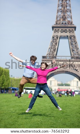 Young couple jumping near the Eiffel tower - stock photo