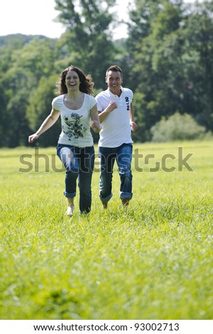 Young couple jumping on a meadow