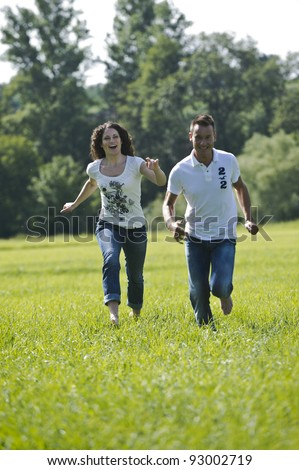 Young couple jumping on a meadow - stock photo