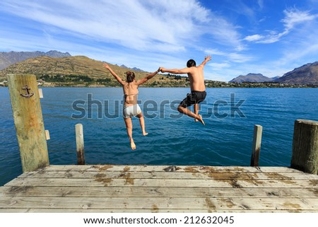 Young couple jumping on the edge of a dock into the Lake Wakatipu - stock photo