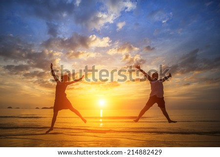 Young couple jumping on the ocean side during amazing sunset. Long-awaited vacation concept. - stock photo