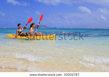 young couple kayaking in hawaii - stock photo