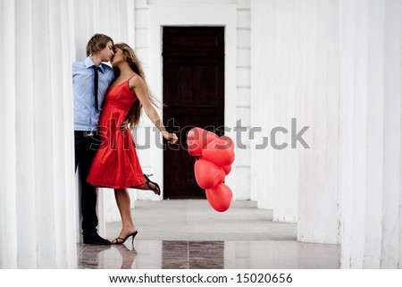 Young couple kissing among white columns and holding bunch of balloons-hearts