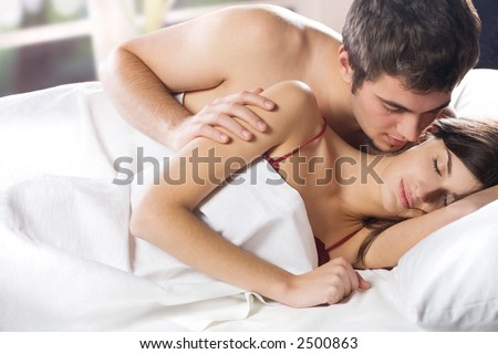 Young couple kissing and hugging on the bed in bedroom - stock photo