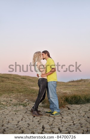 Young couple kissing at meadow in summer evening