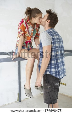 Young couple kissing at new home under construction, woman sitting on iron bar. - stock photo