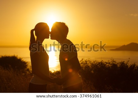 Young couple kissing at sunset - stock photo