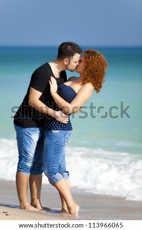 Young couple kissing at the beach. - stock photo