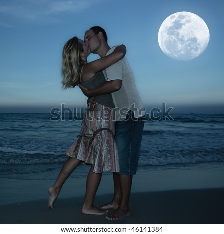Young couple kissing at the beach under moonlight - stock photo