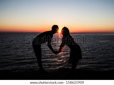 Young couple kissing at the beach with the sun - stock photo