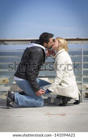 Young couple kissing at wharf and they promises their love with padlock on banister - stock photo