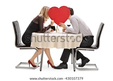 Young couple kissing behind a big red heart seated on a restaurant table isolated on white background - stock photo