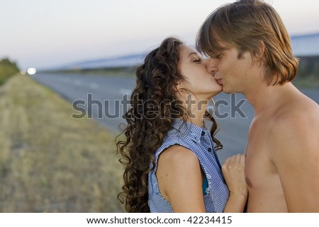 Young couple kissing each other at the edge of a nice road near the sea. - stock photo